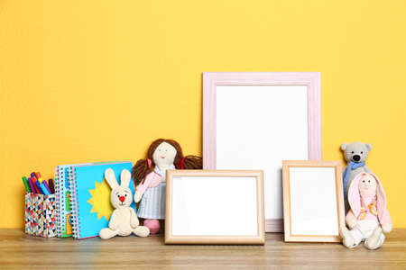 Soft toys and photo frames on table against yellow background, space for text. Child room interior Stockfoto