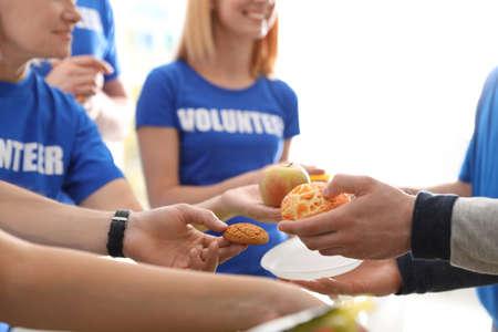 Volunteers serving food to poor people, closeup Stockfoto