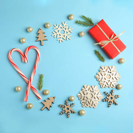 Frame made with Christmas decor on blue background, flat lay. Space for text