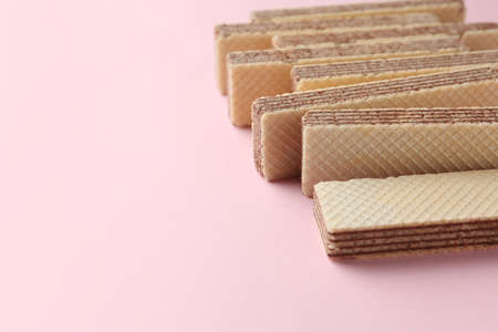 Tasty wafer sticks on pink background, closeup with space for text. Sweet food