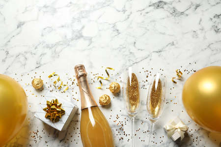 Flat lay composition with bottle of champagne for celebration on white marble background. Space for text Stockfoto