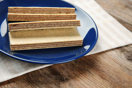 Plate of delicious wafers on brown wooden background. Space for text