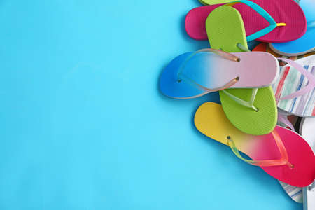 Heap of different flip flops and space for text on blue background, top view. Summer beach accessories