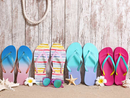 Different bright flip flops and sunglasses on sand near wooden wall, space for text. Summer beach accessories
