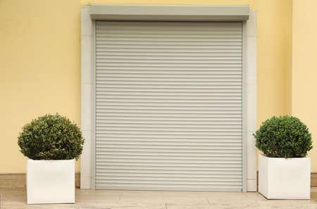 Building with closed roller shutter door. Exterior design 写真素材