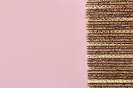 Tasty wafer sticks on pink background, flat lay with space for text. Sweet food Stockfoto
