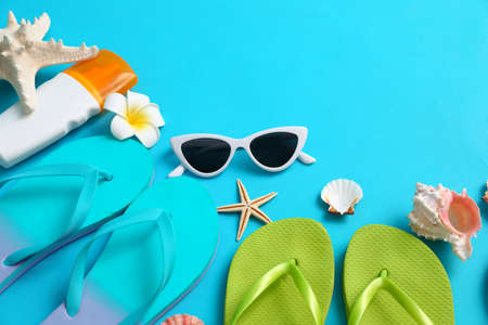 Composition with different flip flops on blue background, space for text. Summer beach accessories