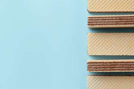 Palitos de obleas sabrosas sobre fondo azul, plano con espacio para texto. Comida dulce