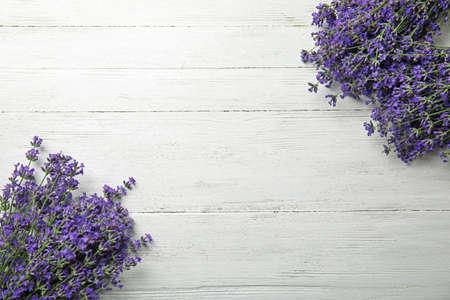 Piękne delikatne kwiaty lawendy na białym drewnianym stole, widok z góry. Miejsce na tekst
