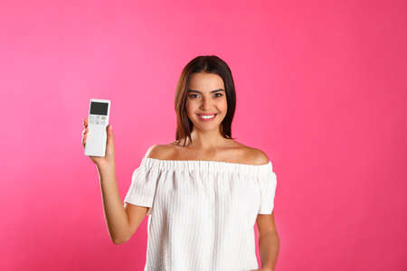 Young woman with air conditioner remote on pink background