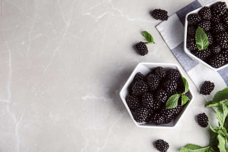 Flat lay composition with tasty blackberries and space for text on grey marble table