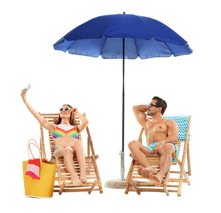 Young couple taking selfie on sun loungers under umbrella against white background. Beach accessories Stock Photo