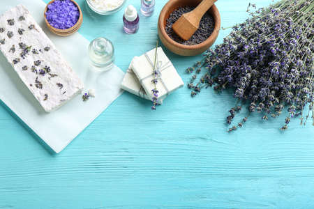 Flat lay composition with hand made soap bars and lavender flowers on light blue wooden table, space for text
