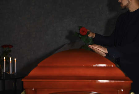 Young man putting red rose onto casket lid in funeral home, closeup