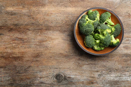 Wooden bowl of fresh broccoli on table, top view with space for text