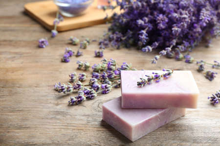 Handmade soap bars with lavender flowers on brown wooden table. Space for text Stockfoto