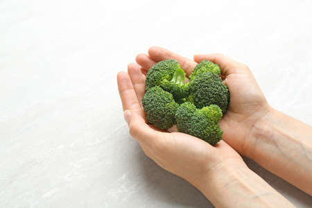 Young woman holding fresh broccoli over light grey table, closeup. Space for text