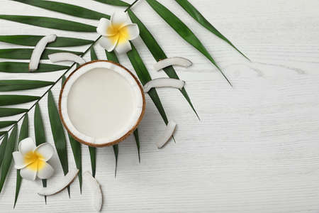 Flat lay composition with half of coconut on white wooden background. Space for text