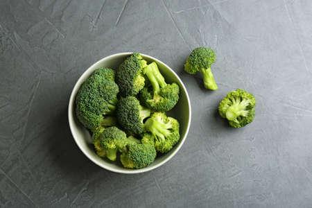 Bowl and fresh broccoli on grey table, flat lay