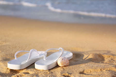 White flip flops and shell on sand near sea, space for text. Beach accessories