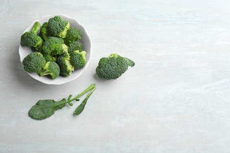Bowl of fresh broccoli and leaves on light grey table, flat lay with space for text 版權商用圖片