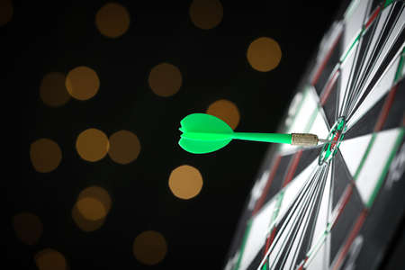 Green arrow hitting target on dart board against blurred lights. Space for text