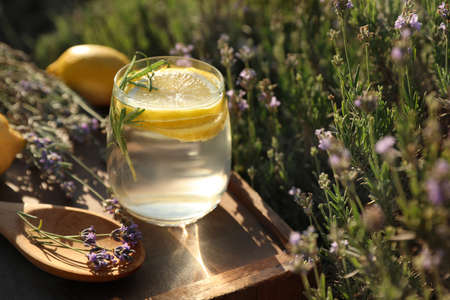 Glass of fresh lemonade on wooden tray in lavender field. Space for text