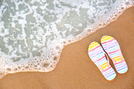Stylish flip flops on sand near sea, top view with space for text. Beach accessories Zdjęcie Seryjne