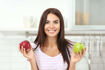 Happy woman holding fresh apples in kitchen