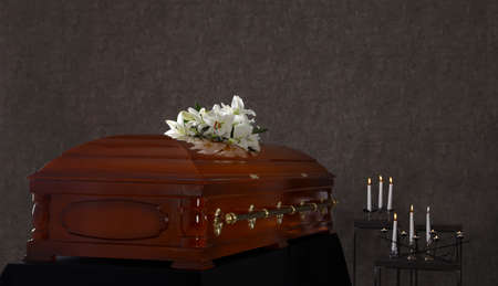 Wooden casket with white lilies in funeral home 写真素材