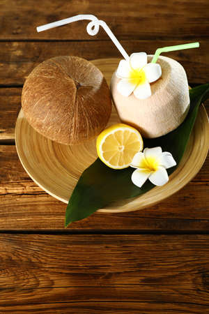 Plate with coconuts and lemon on wooden table
