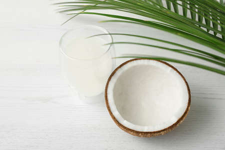 Composition with glass of coconut water on white wooden background