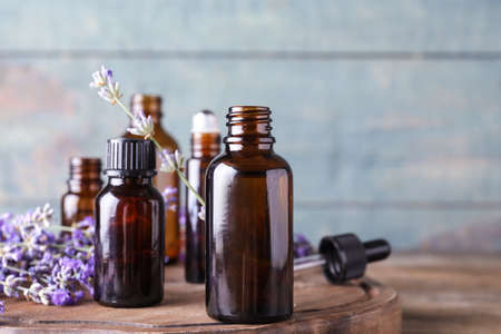 Bottles of essential oil and lavender flowers on wooden table against blue background. Space for text