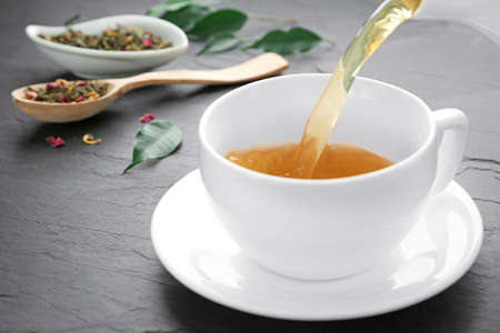 Pouring aromatic tea into cup on black table, closeup