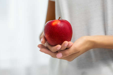 Woman holding fresh red apple on light background, closeup. Space for text Stockfoto