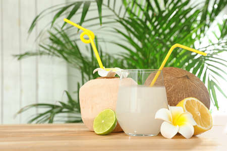 Composition with glass of coconut water on wooden table against blurred background