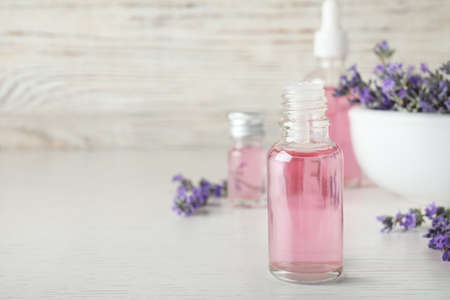 Bottles of essential oil and lavender flowers on white wooden table. Space for text