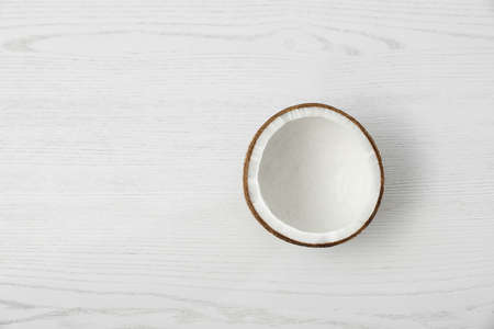 Half of coconut on white wooden background, top view. Space for text Stok Fotoğraf