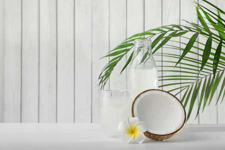 Composition with bottle and glass of coconut water on white wooden table. Space for text Stok Fotoğraf