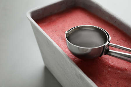 Container with delicious pink ice cream and scoop on grey table, closeup 스톡 콘텐츠