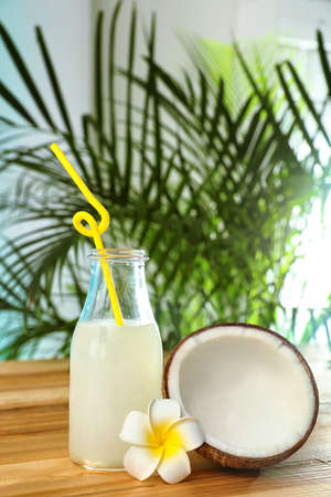 Composition with bottle of coconut water on wooden table against blurred background