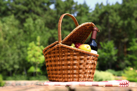 Picnic basket with fruits, bottle of wine and checkered blanket on wooden table in garden