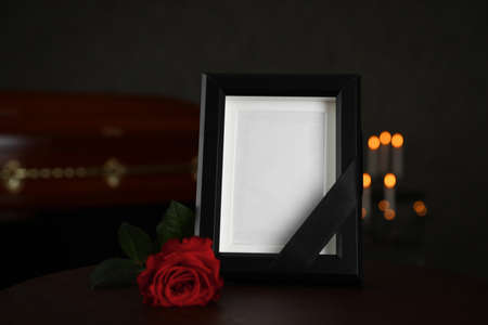Black photo frame and red rose on table in funeral home
