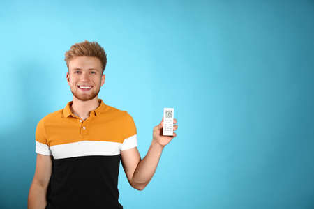 Young man with air conditioner remote on blue background. Space for text