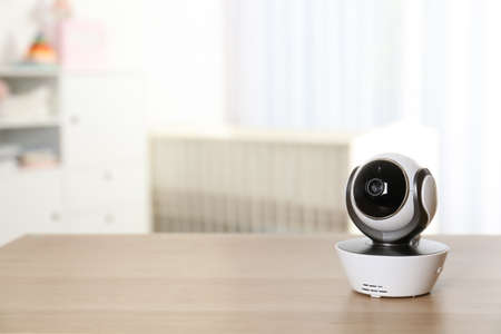 Baby camera on table in room, space for text. Video nanny