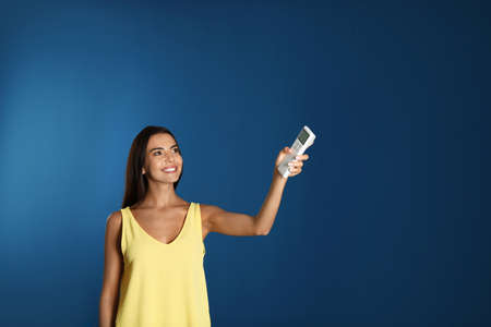 Young woman turning on air conditioner against blue background Stock Photo - 128827198