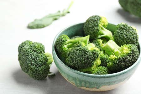 Bowl and fresh broccoli on light grey table, closeup Imagens