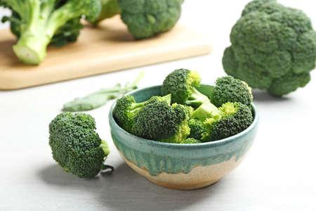 Bowl and fresh broccoli on light grey table