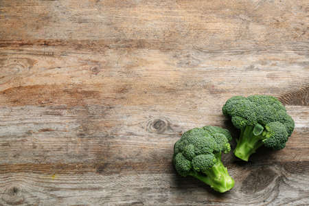 Fresh raw broccoli florets on wooden table, top view with space for text