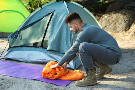 Young man with sleeping bag near tent outdoors Imagens